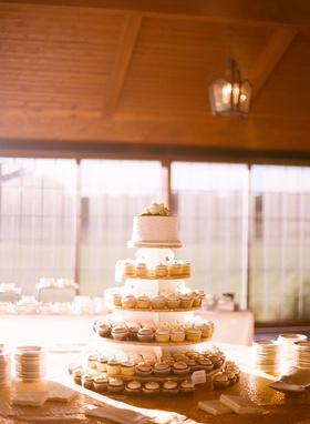 Wedding with cupcakes arranged to look like cake tiers topped with at white cake