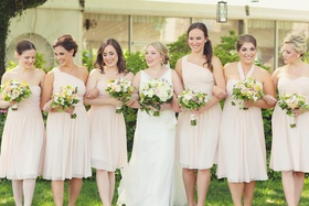 Bride with girlfriends outside holding bouquets