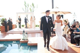 Bride in mermaid dress and groom holding hands