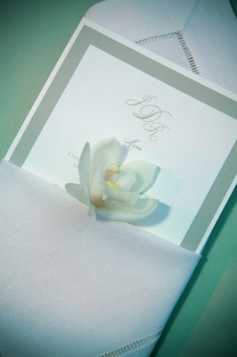Wedding reception dinner menu with a light green border in a white cloth napkin with an orchid