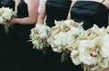 bridesmaids wearing black gowns hold white flowers