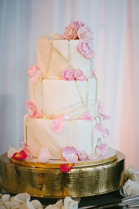 Three layer wedding cake with sugar petals and tulle