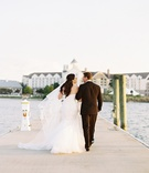 Bride and groom walking on plank in wedding attire