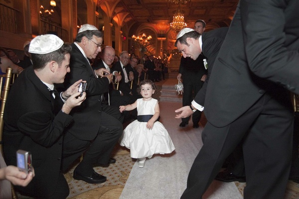 Flower girl walks down the aisle in a sleeveless satin gown with a black sash