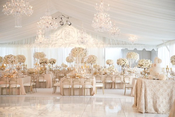 Tent wedding reception with white flowers and gold chairs
