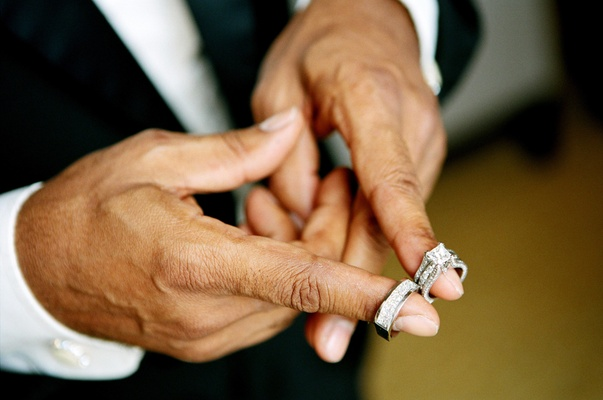 African American groom with wedding rings on fingers