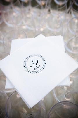 Black circle monogram on white drink napkin