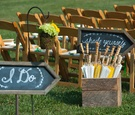 Wood ceremony chair at outdoor wedding and chalkboard signs