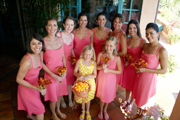 Bridesmaids in coral dresses with yellow flower girl