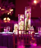 Wedding reception table with submerged white calla lilies and tulips, floating candles