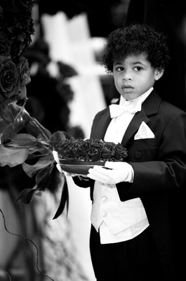 Black and white photo of boy wearing tux and gloves