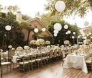 Paper lanterns suspended over long guest tables