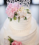 Wedding cake with fresh pink and white peonies, greenery, and cake topper with couple's last name