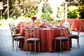 Wedding reception table with red tablecloth and golden chiavari chairs with plum cushions