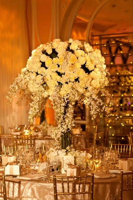 Gold chairs around table topped with large arrangement