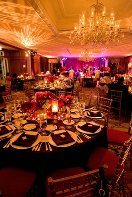 Gold chairs with red cushions around brown tablecloths