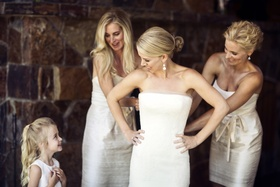 Women in white dresses helping bride get dressed