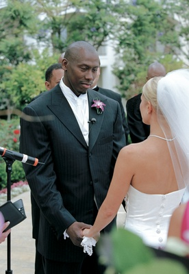 Al Joyner in suit at wedding holding hands