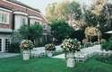 white chairs and urns of flowers set up in backyard