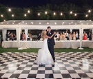 Bride in a strapless Hayley Paige dress dances with groom in black tuxedo