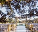 White ceremony under oak tree near lake in Texas