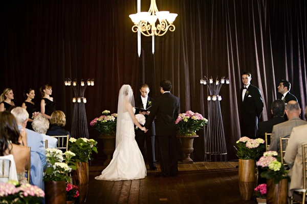 ceremony with candles, pink flowers and brown drapery
