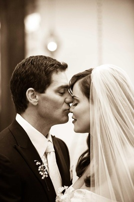 Black and white photo of groom kissing bride's nose