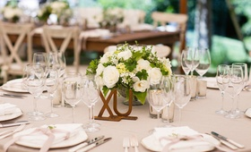 Brass letters on table with small flower arrangement