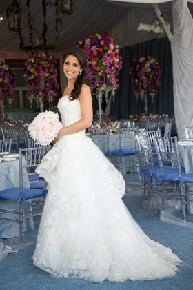 Bride in a strapless Monique Lhuillier dress with floral appliques holds a bouquet of light flowers