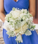 Bridesmaid in blue holding white flowers and greenery