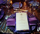 Purple charger plate on copper sequin tablecloth at wedding