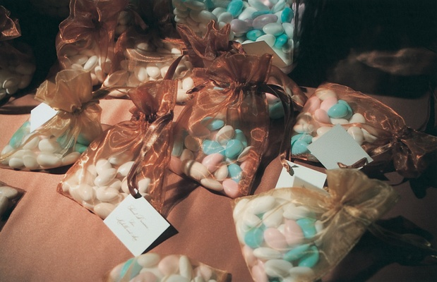 Blue, pink, and white jordan almonds in gold and brown sheer bags