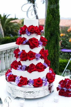 white cake with red roses and purple flowers on tiers and crystal C