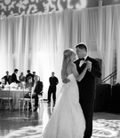 Black and white photo of bride in a strapless gown dancing with groom in a tuxedo