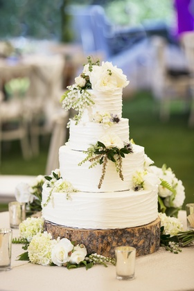 White round cake on wooden slice with flowers