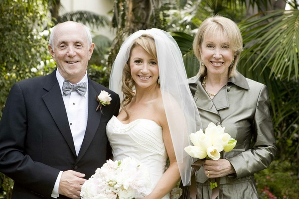 Bride with father and mother of bride in metallic trench coat