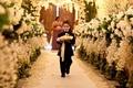 Little boy walking down floral-embellished aisle