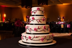 White round wedding cake with cherry blossom design and black ribbon details