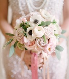 Bride's bouquet of white anemones and ranunculus, and pink roses and lisianthus