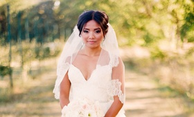 Bride in a lace dress with spaghetti straps and veil with floral details holds a bouquet