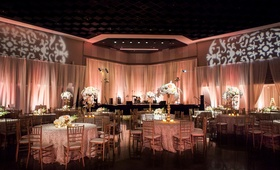 Wedding reception with peach uplighting, white centerpieces, round tables and golden chairs