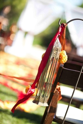 A lantern, red and orange ribbons with yellow flowers suspended on a hook for an outdoor wedding