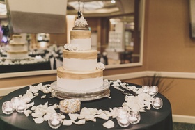 White round cake with gold paint and fresh flowers