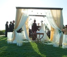 Alfresco ceremony with drapery and petals