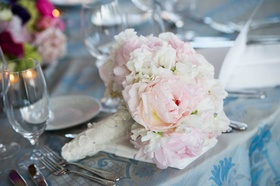 Bride's bouquet of white and pink peonies wrapped in fabric with floral appliques