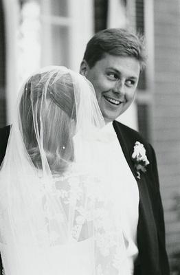 groom smiles at bride wearing wedding veil