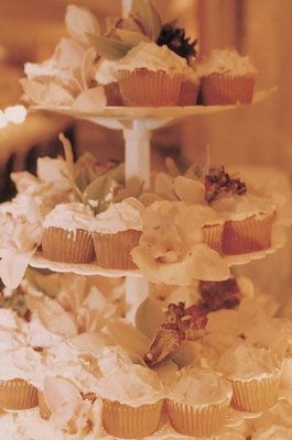 Three-tiered white cake stand with cupcakes