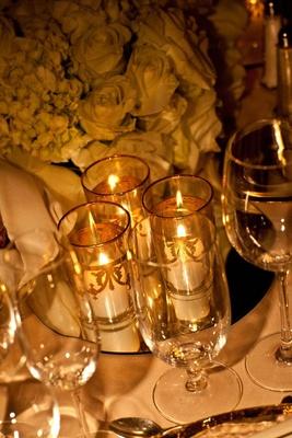 White votive candles in gilt pillar vases