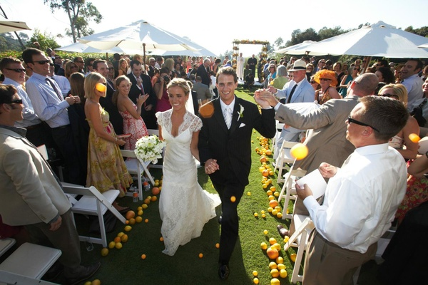 Bride and groom walk up aisle with fruit and ping pong balls