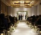 Bride and groom beneath flower chuppah in white ballroom